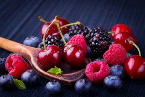 Cherries and berries on wooden spoon